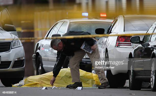 Officer investigates the scene where a body lies at the scene where two Santa Ana police officers were involved in an officerinvolved shooting that...