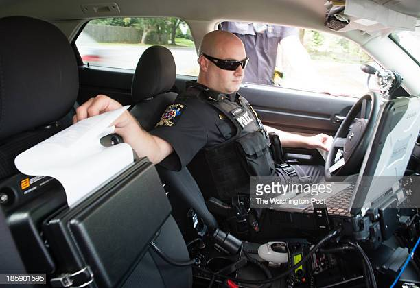 Officer Jeff Innocenti pulls a ticket from his printer during a traffic stop for cell phone use Montgomery County Maryland police officers work to...