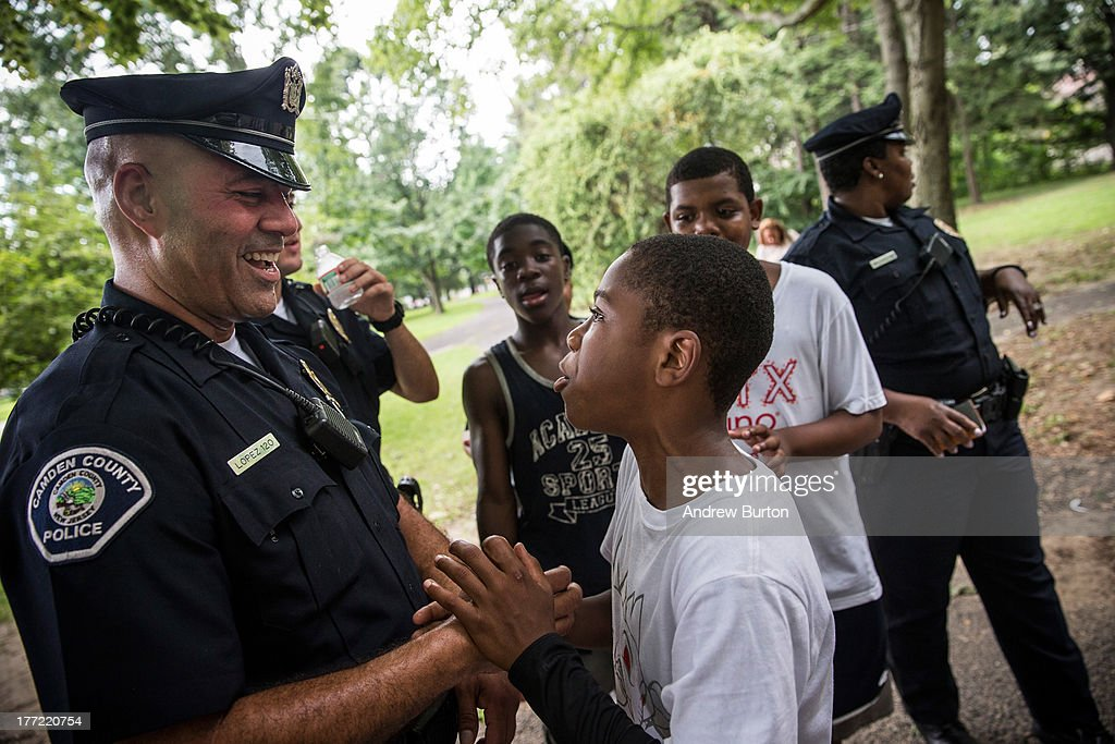 Officer Jim Lopez (L), of the Camden County Police Department (CCPD), wrangles with Omar Headen, age 13, during a day of action, organized by the CCPD, which included neighborhood interaction and the cleaning of Farnham Park, on August 22, 2013 in the Parkside neighborhood of Camden, New Jersey. The town of Camden, which was once a large industrial town but watched it's population dwindle as manufacturing left, has been marred with societal problems including high unemployment, crime, murder and heavy drug trafficking for decades. The Camden County Police Department was officially created in May, 2013, after the unionized Camden Police department was disbanded. The overhaul, which was supported by New Jersey Governor Chris Christie, has been considered unprecendented and has been closely watched around the country. The new force currently has approximately 280 members, and will reach full size by December, with 400 members. Early signs suggest the overhaul has been effective - The Wall Street Journal reported earlier this month that Camden murder rates fell 29% from May, 2013 to July 2013, compared to the same period last year. Absentee rates of the CCPD is also lower: approximately 5% of officers have been reported absent so far, compared to approxmiately 30% of the Camden Police Department prior to the change in command.