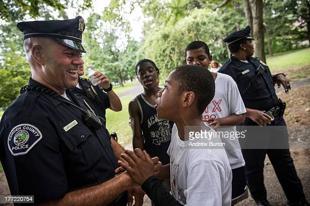 Officer Jim Lopez , of the Camden County Police Department , wrangles with Omar Headen, age 13, during a day of action, organized by the CCPD, which...