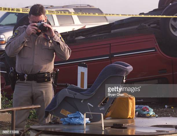 CHP officer Joe Davy photographs a child seat as he investigates the crash of a Ford Taurus and Ford Explorer at the intersection of 5th and Las...