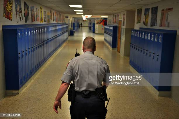 Officer Joe Plazio, of the Fairfax County Police Department, patrols the hallways where he is stationed at West Springfield High School on Friday,...