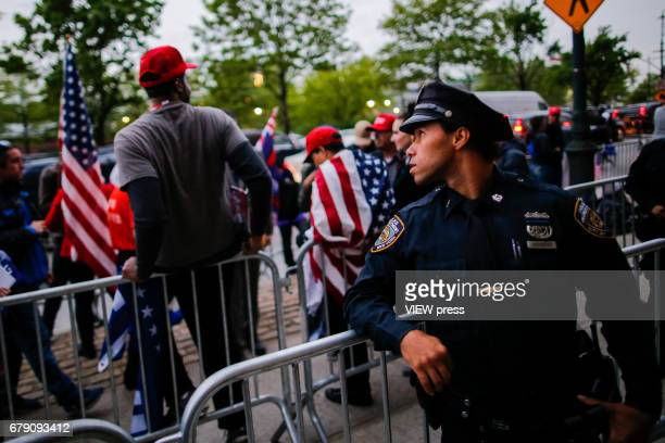 A NYPD officer keeps an eye on activists as they protest near the USS Intrepid where US president Donald Trump is hosting the visit of Australian...