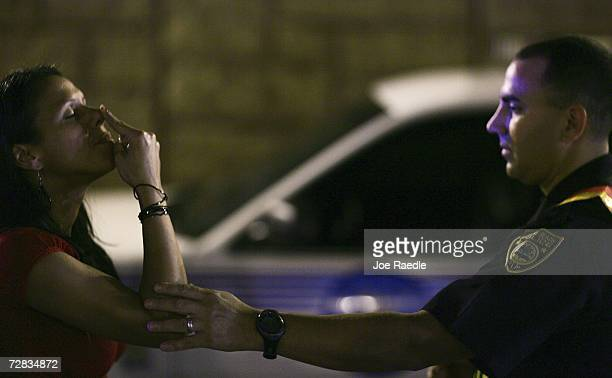 Officer Kevin Millan from the City of Miami Beach police department helps steady a woman during a field sobriety test at a DUI sobriety traffic...