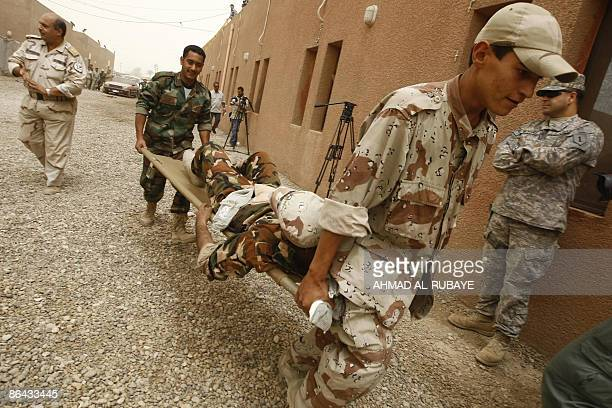 A US officer looks on as Iraqi military rescue officers carry a stretcher as they are put through their paces during a training session on emergency...