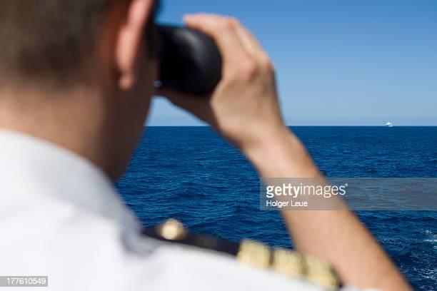 Officer looks through binoculars with cruise ship