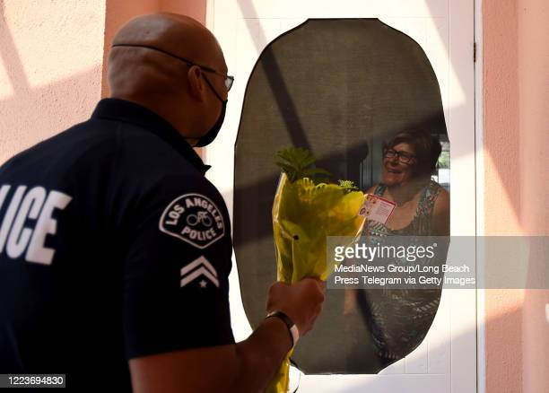 Officer Maligi Nua delivers flowers to Jerryne Soto in recognition of Mother's Day in San Pedro on Friday May 8 2020 The women were nominated and the...
