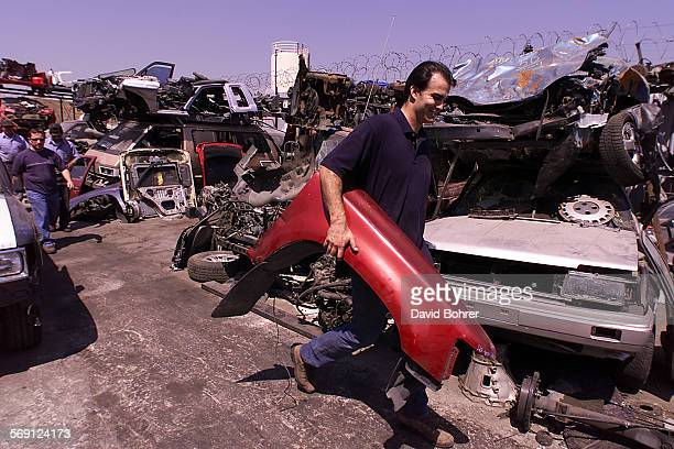 LAPD officer Matthew Bygum carries the right front panel of a stolen car that was in pieces throughout an auto dismantling business in Sun Valley...