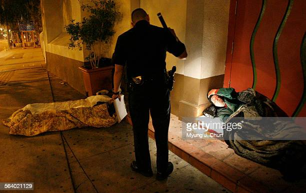 LAPD officer Mike Fernandez conducts a census check of the homeless sleeping on Main Street at Our Lady Queen of Angels Church in Los Angeles early...