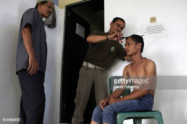 Officer of civil service police and Wilayatul Hisbah Banda Aceh cutting the hair of one of the transgenderers who was arrested in Banda Aceh Aceh...