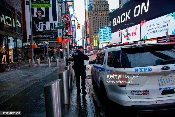 A NYPD officer patrols Times Square as rain falls on March 28 2020 in New York City US President Donald Trump said on March 28 2020 that he's...