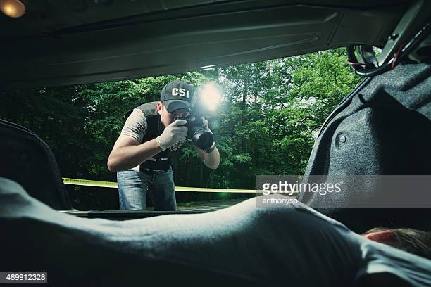 CSI officer photographing body in trunk of car