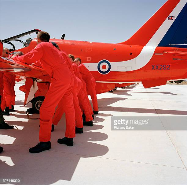 Officer pilots of the elite 'Red Arrows' Britain's prestigious Royal Air Force aerobatic team lean against a wing of their Hawk jet in a preflight...