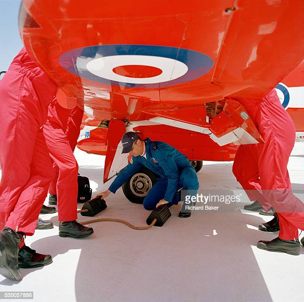 Officer pilots of the elite 'Red Arrows' Britain's prestigious Royal Air Force aerobatic team lean aginst a wing of their Hawk jet in a preflight...