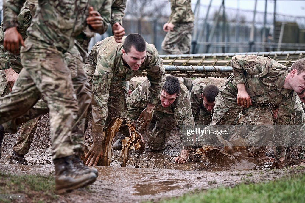 Officer recruits run under a cargo net on the Tarzan assault course during training at Commando Training Centre Royal Marines on December 01, 2014 in Lympstone, United Kingdom. Recruit training lasts for 32 weeks for Marines and 64 weeks for officers and is one of the longest and most physically demanding specialist infantry training regimes in the world. On the 28th October 2014, the Royal Marines celebrated their 350th birthday year. Since then, Marines have taken part in more battles on land and sea around the world than any other branch of the British Armed Forces.