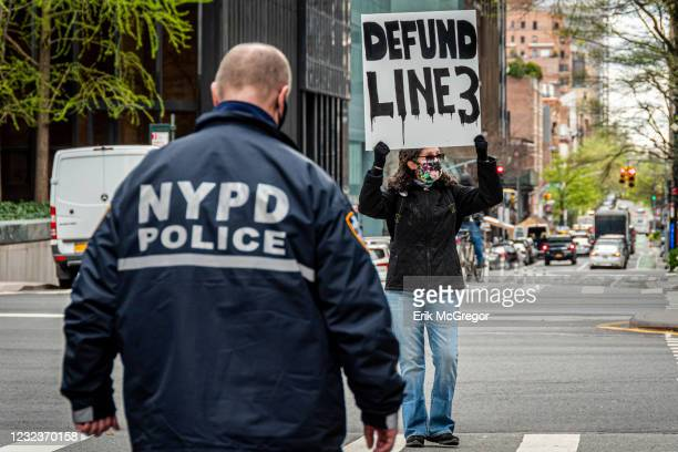 Officer seen approaching a participant blocking a street while holding a sign at the protest. Climate activists with Stop the Money Pipeline held a...