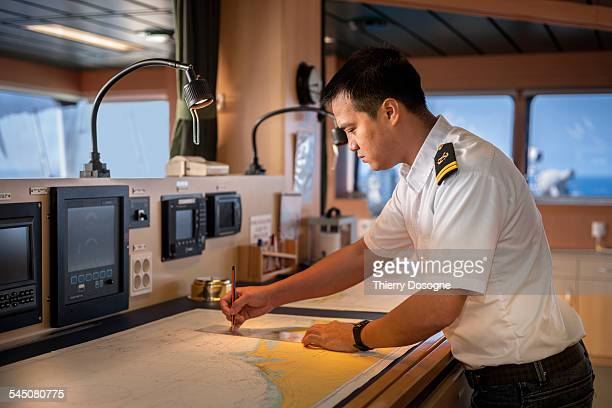 Officer ship drawing maritime road on map
