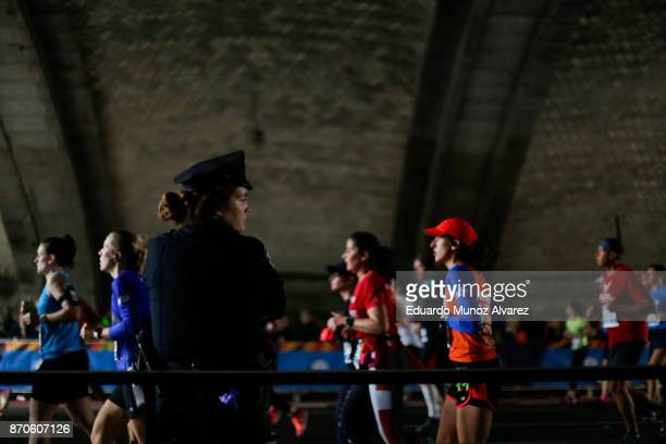 NYPD officer stands guard as runners make their way under the Ed Koch Queensboro Bridge during 2017 TCS New York City Marathon November 5 2017 in New...