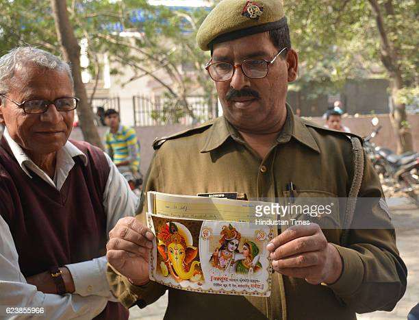 PAC officer stands in queue outside bank holding his child's wedding card in hope to withdraw Rs 25 lakh for the wedding on November 17 2016 in...