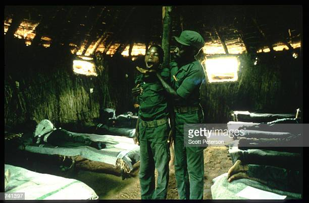 UNITA officer stands with a young soldier January 23 1990 near Jamba Angola The National Union for the Total Independence of Angola and the Marxist...