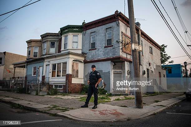 Officer Tom Rambone, of the Camden County Police Department , goes on a foot patrol on August 20, 2013 in the East Camden neighborhood of Camden, New...