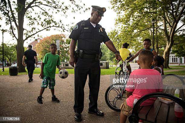 Officer Troy Redd, of the Camden County Police Department , plays with children on August 20, 2013 in the Fairview neighborhood of Camden, New...
