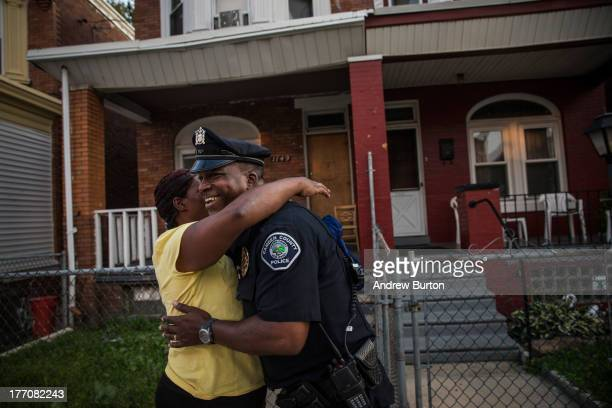 Officer Troy Redd, of the Camden County Police Department , talks with a woman while on a foot patrol on August 20, 2013 in the East Camden...