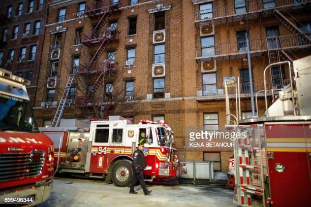 A NYPD officer walks on the scene of an apartment fire in the Bronx borough of New York City on December 29 2017 Officials said Friday that the death...