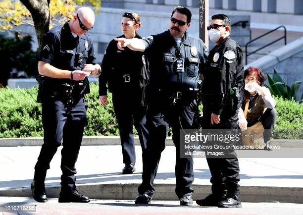 Officer wearing a mask speaks fellow officers as they take a report after a car accident at Spring St. And Temple st. In Los Angeles on Friday, April...