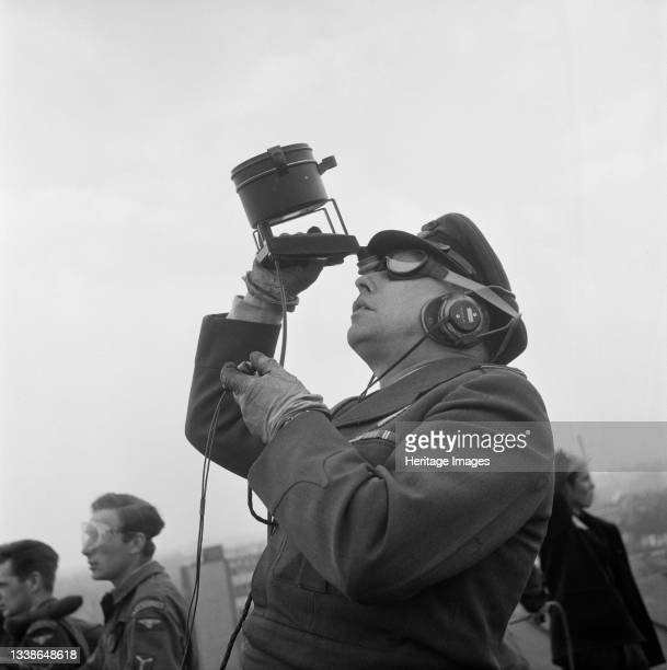 Officer with a hand held signal lamp standing on the roof of Coventry Cathedral during the lowering of the 80ft bronze spire. The photograph was...