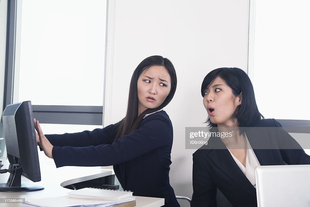 Officer worker hiding her computer from coworker : Stock Photo