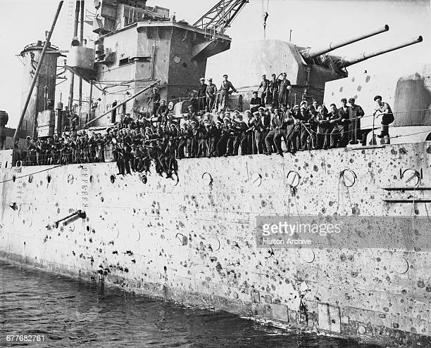 Officers and crew line the deck of the bomb splinter damaged starbord side of the Royal Navy Arethusaclass light cruiser HMS Penelope which was also...