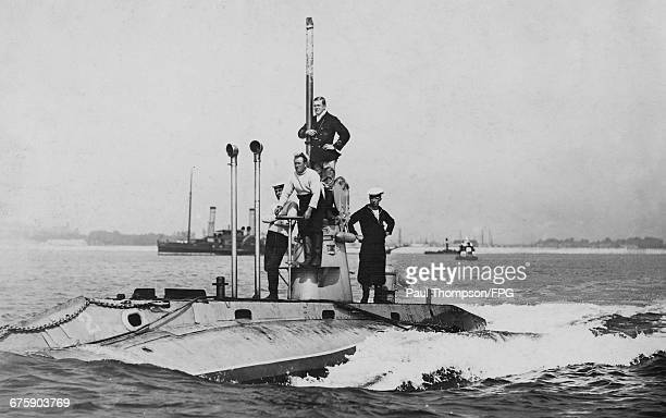 Officers and crew stand on deck around the conning tower of the second Royal Navy Hollandclass submarine HMS Holland 2 on patrol entering Fort...