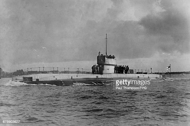 Officers and crew stand on deck around the conning tower of the Royal Navy E-class submarine HMS E3 while on patrol entering Fort Blockhouse...