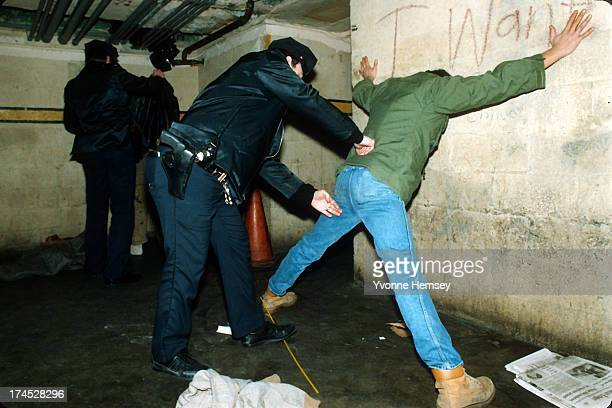 NYPD officers are photographed January 12 1988 frisking a man presumed to be homeless near Port Authority in New York City