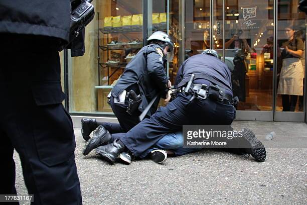 Officers arrest a protester during a May Day march through midtown while people inside an eatery look on