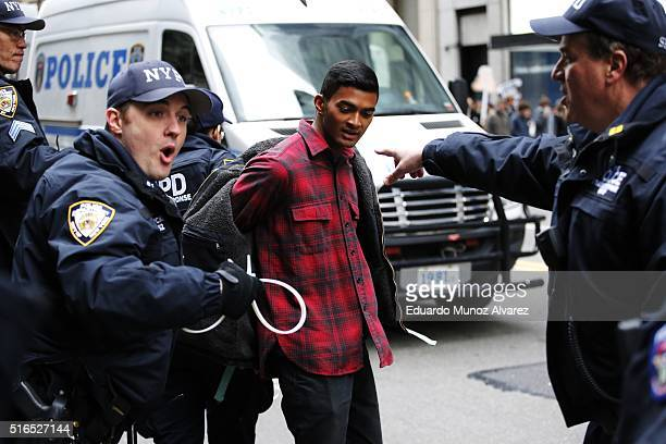 NYPD officers arrest a protester while they take part in a demonstrations against Republican presidential candidate Donald Trump on March 19 2016 in...