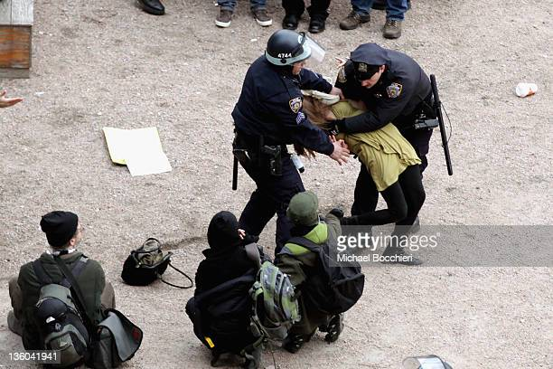 Officers arrest a woman after activists gained entrance to a private park owned by Trinity Church next to Duarte Square at Sixth Avenue and Canal...