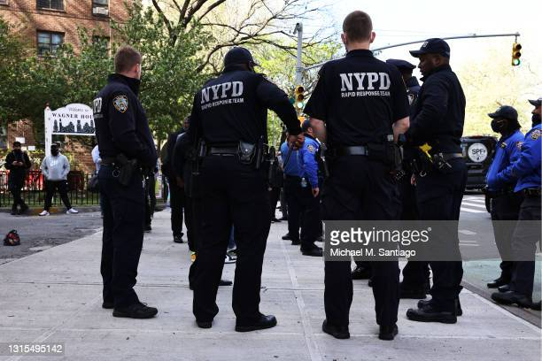 Officers await the start of a peace walk to denounce the rise of gun violence in the city in the Harlem neighborhood on April 30, 2021 in New York...