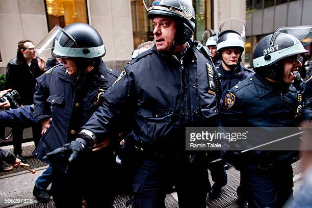 NYPD officers block demonstrators as they arrest a protestor with Occupy Wall Street movement near Wall Street during the day long confrontations...