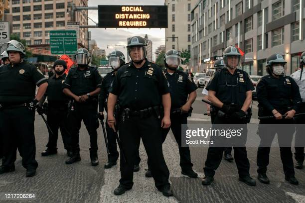 Officers block the entrance of the Manhattan Bridge as hundreds protesting police brutality and systemic racism attempt to cross into the borough of...