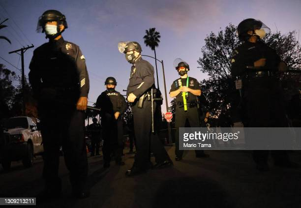 Officers block the street near Echo Park Lake as protesters demonstrate nearby against the removal of a homeless encampment on March 25, 2021 in Los...