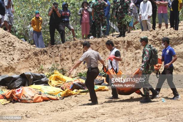 Officers bring the bodies of victims of the earthquake and tsunami in Palaroa village in the city of Palu Central Sulawesi Indonesia on October 1...