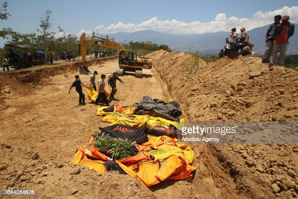 Officers bring the bodies of victims of the earthquake and tsunami to bury them in Palaroa village in the city of Palu Central Sulawesi Indonesia on...