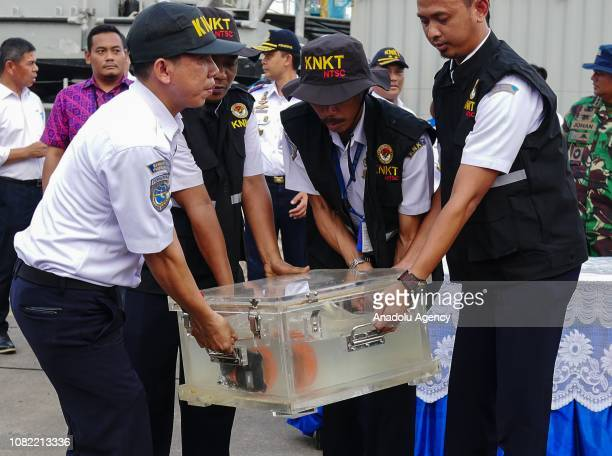 Officers bring the cockpit voice recorder of the crashed Lion Air JT610 kept in a waterfilled container during a press conference at Tanjung Priok...