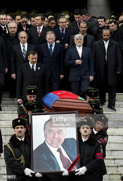 Officers carry the portrait and the coffin of former President Geidar Aliev prior to his civil funeral December 15 2003 in Baku Azerbaijan The...