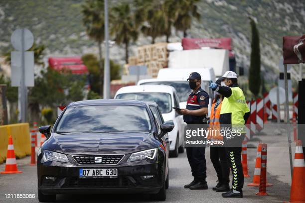 Officers check vehicles and body temperature of drivers at entrance and exit of the city after the Turkish government lifted the coronavirus travel...