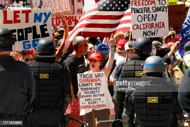 Officers dressed in riot gear prepare to remove protesters from the California Capitol grounds during a protest rally held on Friday, May 1, 2020....