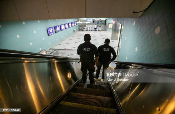 Officers E. Rosales, left, and D. Castro, patrol the Metro Red Line Hollywood/Highland Metro Station as tourists pass by Thursday, June 25, 2020 in...