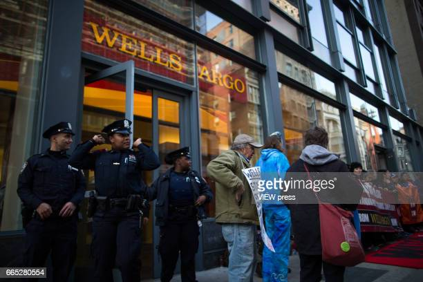 NYPD officers exit the Wells Fargo bank as indigenous peoples and activists begin the overnight camp out in front of the branch on April 5 2017 in...